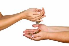 Las manos femeninas vierten abajo de monedas en otra persona Fotos de archivo libres de regalías
