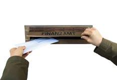 Las manos fijan una letra en la caja de letra de oficina de las finanzas, Finanzamt fotografía de archivo