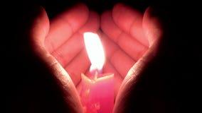 Las manos forman como un corazón para proteger una vela ardiente almacen de metraje de vídeo