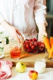 Las manos hacen los smoothies de la fresa en tabla de madera Strawbe fresco Foto de archivo