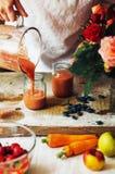 Las manos hacen los smoothies de la fresa en tabla de madera Strawbe fresco Fotos de archivo