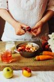 Las manos hacen los smoothies de la fresa en tabla de madera Strawbe fresco Fotografía de archivo