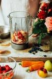 Las manos hacen los smoothies de la fresa en tabla de madera Strawbe fresco Imagen de archivo libre de regalías