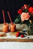 Las manos hacen los smoothies de la fresa en tabla de madera Strawbe fresco Fotos de archivo libres de regalías