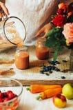 Las manos hacen los smoothies de la fresa en tabla de madera Strawbe fresco Foto de archivo libre de regalías