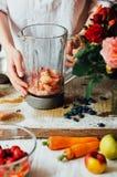 Las manos hacen los smoothies de la fresa en tabla de madera Strawbe fresco Imagenes de archivo