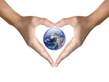 Las manos hacen que el corazón forma la cubierta la tierra Imagen de archivo