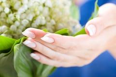Las manos hermosas con el manojo de pueden lirio Foto de archivo libre de regalías