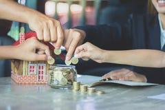 Las manos humanas insertan la moneda en un tarro de cristal, tarro o completo del dinero de los ahorros foto de archivo libre de regalías