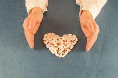 Las manos humanas protegen al guardia que una forma del corazón hizo de píldoras Fotografía de archivo libre de regalías