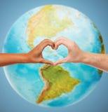 Las manos humanas que muestran el corazón forman sobre el globo de la tierra Fotografía de archivo libre de regalías