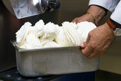 Las manos humanas sostienen el envase de acero lleno de helado del sabor de la vainilla Fotografía de archivo