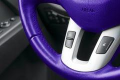 Las manos liberan y los medios botones del control en azul volante adentro el cuero negro, detalles modernos del interior del coc foto de archivo