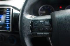 Las manos liberan y los medios botones del control en el volante Fotos de archivo