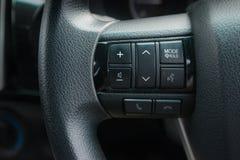 Las manos liberan y los medios botones del control en el volante Fotografía de archivo