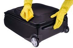 Las manos limpian la maleta imagen de archivo