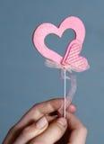Las manos llevan a cabo corazones rosados de la tarjeta del día de San Valentín en fondo azul Foto de archivo libre de regalías