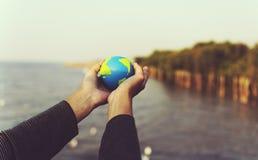Las manos llevan a cabo la ecología verde global del ambiente imagenes de archivo