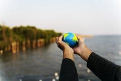 Las manos llevan a cabo la ecología verde global del ambiente imagen de archivo