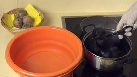 Las manos llevan los huevos pintados del agua del pote con la pintura el cuenco anaranjado con agua metrajes