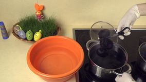 Las manos llevan los huevos pintados del agua del pote con la pintura el cuenco plástico con agua almacen de metraje de vídeo