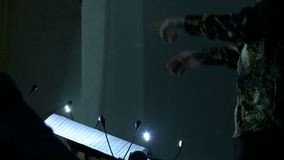 Las manos móviles de un conductor de orquesta que dirige a los músicos Tiro del primer metrajes