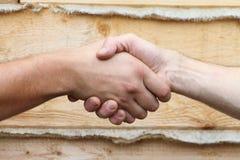 Las manos masculinas bronceadas hacen el apretón de manos imágenes de archivo libres de regalías