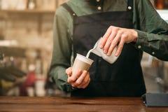 Las manos masculinas completan una taza de leche Fotografía de archivo