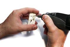 Las manos masculinas con el grabador cortaron el colgante hecho del hueso en un CCB blanco Imágenes de archivo libres de regalías