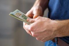 Las manos masculinas con los billetes de banco se cierran para arriba imagen de archivo libre de regalías