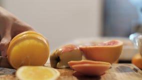 Las manos masculinas cortaron el limón amarillo con un cuchillo en la tajadera Vector festivo Preparación por el Año Nuevo metrajes