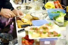Las manos masculinas de los cocineros hacen el bocadillo delicioso en la tabla Imagen de archivo