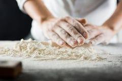 Las manos masculinas del cocinero amasan la pasta con la harina en la tabla de cocina imagen de archivo