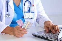 Las manos masculinas del doctor de la medicina sostienen píldoras y mecanografían algo en el teclado de ordenador portátil Reserv Fotos de archivo