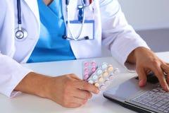 Las manos masculinas del doctor de la medicina sostienen píldoras y mecanografían algo en el teclado de ordenador portátil Reserv Foto de archivo libre de regalías