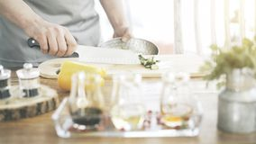 Las manos masculinas del ` s de la cocina están poniendo los pepinos tajados a un cuenco fotografía de archivo