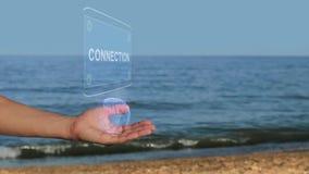 Las manos masculinas en la playa llevan a cabo un holograma conceptual con la conexión del texto metrajes