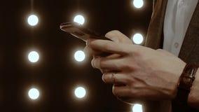 Las manos masculinas enrollan el servicio de noticias en smartphone almacen de metraje de vídeo