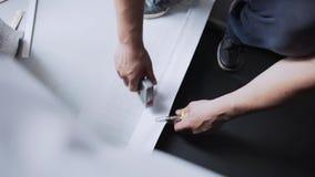 Las manos masculinas están conduciendo grapas pesadas en los papeles pintados blancos por el grapa-arma almacen de metraje de vídeo