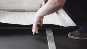 Las manos masculinas están conduciendo grapas pesadas en los papeles pintados blancos por el grapa-arma metrajes