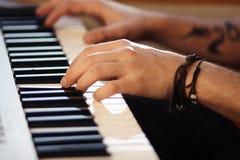 Las manos masculinas hermosas juegan en el sintetizador moderno imagenes de archivo