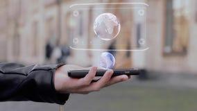 Las manos masculinas muestran en la tierra conceptual del planeta del holograma de HUD del smartphone metrajes
