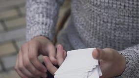 Las manos masculinas pasan dominante una cubierta de tarjetas almacen de video