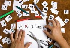 Las manos masculinas pusieron juntas cartas en la palabra - crimen. Fotografía de archivo