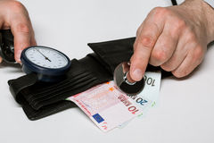 Las manos masculinas pusieron un estetoscopio a la caja con el dinero euro Fotografía de archivo libre de regalías