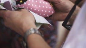 Las manos masculinas que eligen el paño modelan pasar a través de muestras almacen de metraje de vídeo