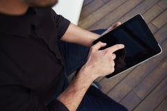 Las manos masculinas que sostienen la pantalla táctil hacen tabletas la PC con la pantalla del blanc Foto de archivo libre de regalías