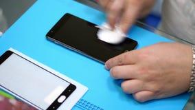 Las manos masculinas que sostienen y que limpian una pantalla del teléfono móvil para poner, aplican un vidrio moderado protector metrajes