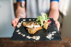 Las manos masculinas sostienen el plato del prendedero de pescados frito Foto de archivo libre de regalías