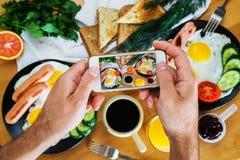 Las manos masculinas toman una imagen de un desayuno americano en la opinión superior del teléfono Foto de archivo